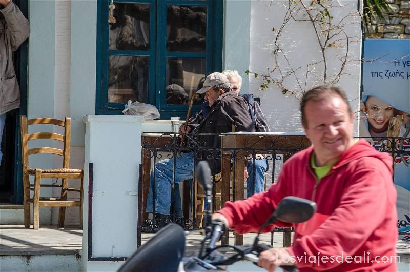 un hombre pasa en moto sonriente delante de terraza donde hay dos ancianos al sol en pueblos del interior de naxos