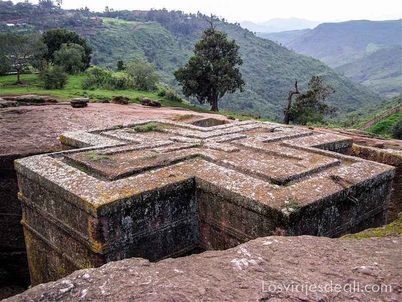 iglesia en forma de cruz excavada en la roca de la montaña y al fondo valle verde