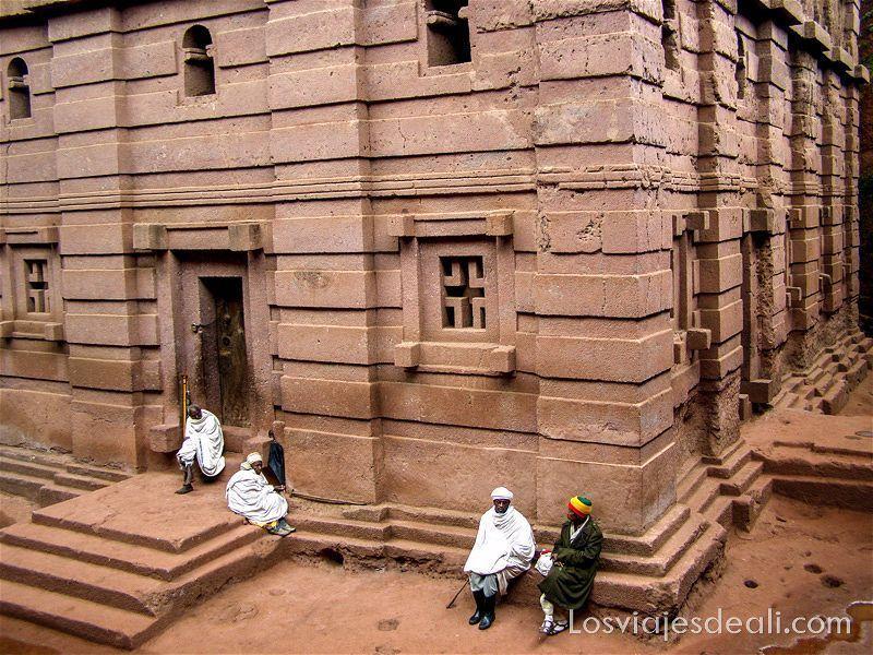 iglesias con cuatro hombres sentados en la puerta iglesias de lalibela