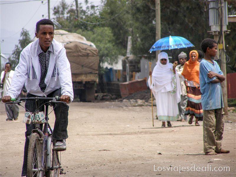 un chico montando en bicicleta y dos mujeres más atrás con paraguas azul en lalibela