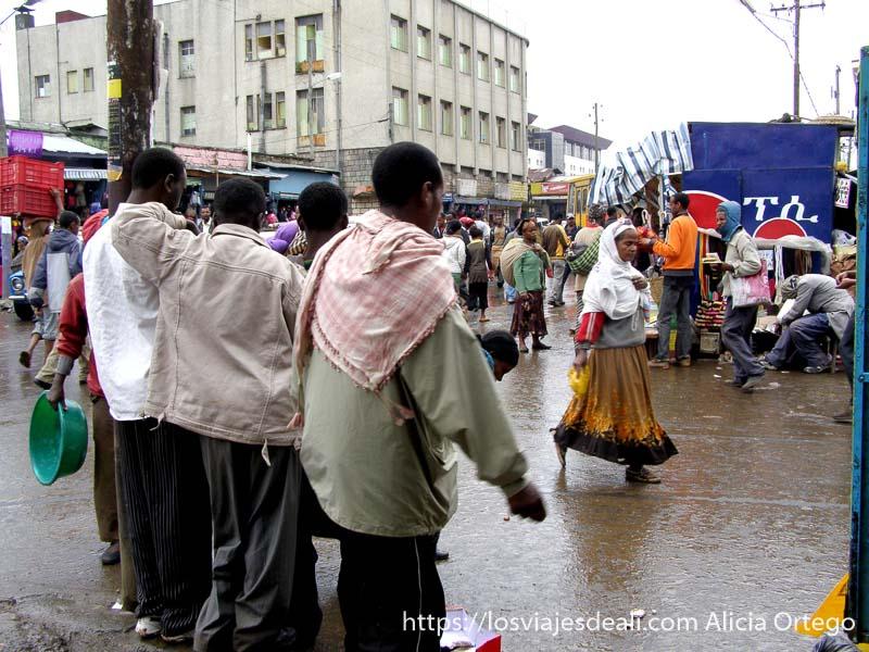 hombres apoyados en una farola mirando la calle llena de gente en lalibela etiopía diferentes.leyu