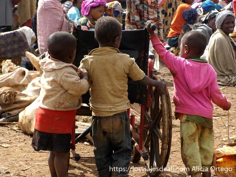 tres niños pequeños empujando una silla de ruedas vacía en medio del mercado dorze en etiopía