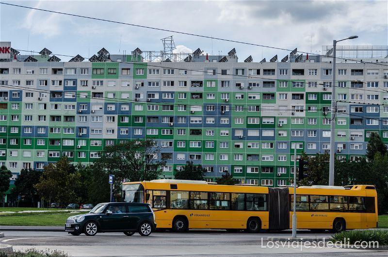 bloques de casas soviéticas pintadas de verde y azul y un bus amarillo pasando delante en óbuda