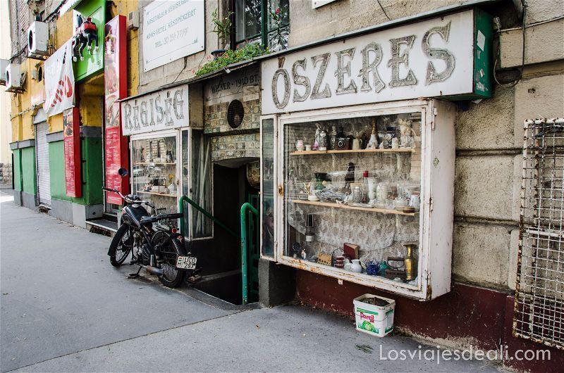 antiguo comercio de óbuda en budapest  con una moto antigua en la puerta
