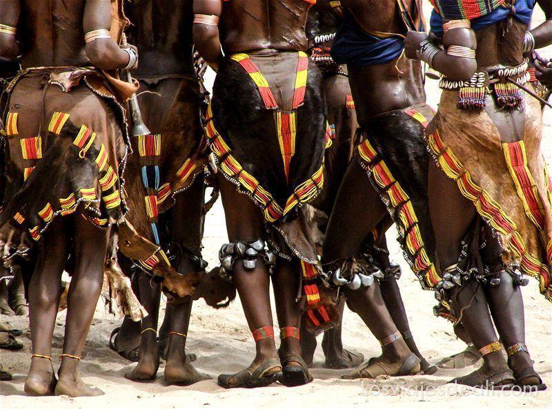 mujeres de la tribu hamer bailando en corro con faldas de piel y bolitas de color rojo y amarillo, cascabeles en las piernas