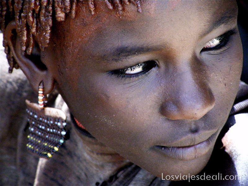 retrato de una niña de la tribu hamer con un gran pendiente de bolitas de colores y ojos muy negros