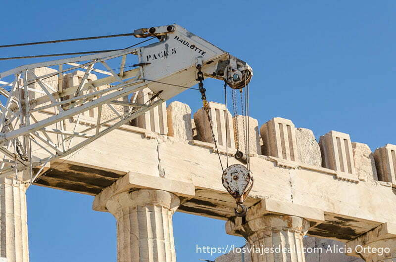 grúa y columnas del partenón detrás con cielo muy azul en la acrópolis de atenas