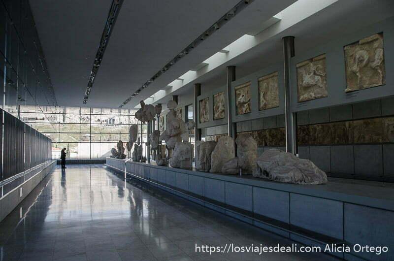 pasillo del museo con grandes esculturas acrópolis de atenas y su museo