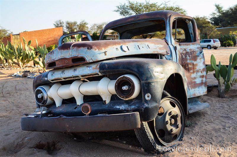 coche de los años 20 oxidado junto a unos cactus en solitaire