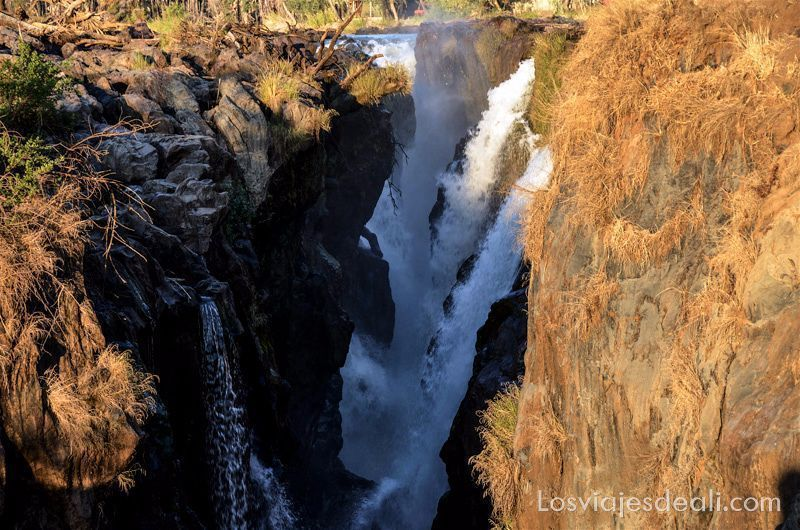 agua cayendo en un cañón de roca con luz de atardecer en las cataratas epupa