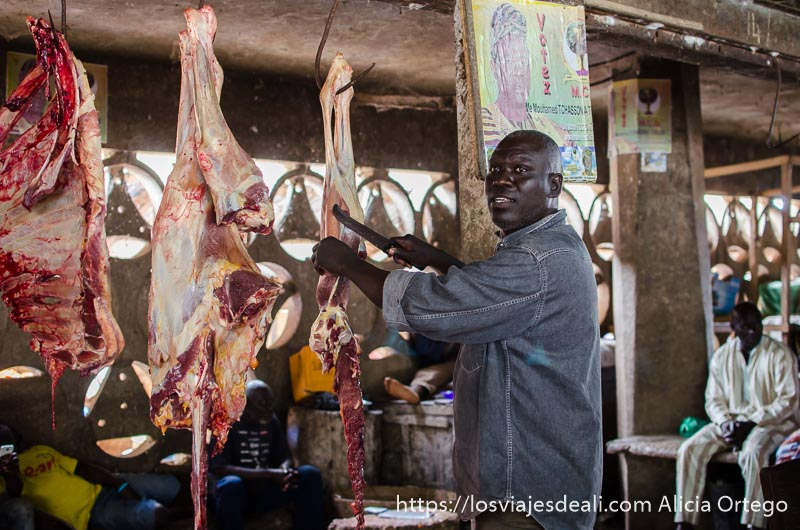 carnicero cortando carne en su puesto del mercado ruta por el interior de togo