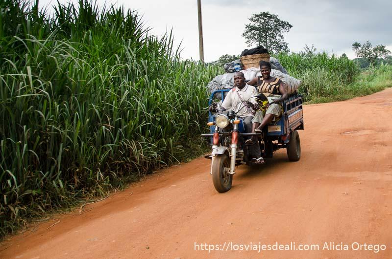 pareja en una moto con carro lleno de cosas ruta por el interior de togo