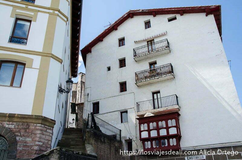 casa de cuatro pisos de fachada blanca y ventanas rojas que está como inclinada junto a escaleras