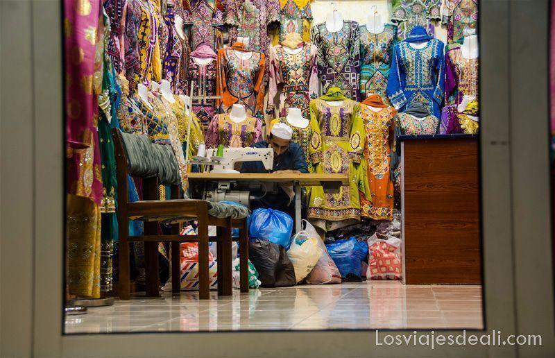 sastre omaní en su tienda trabajando con la máquina de coser y rodeado de muchos vestidos de colores de mujer mercados del mundo