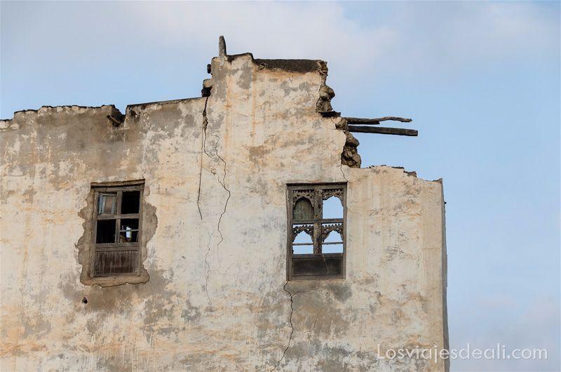 fachada de edificio de Omán destruida pero con ventanas de celosías de madera puertas y ventanas del mundo