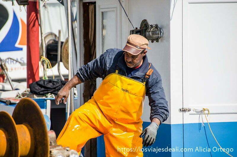 pescador con mono amarillo saliendo de su barco de pesca en la capital de naxos