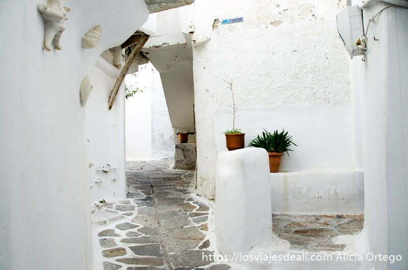 calle de la capital de naxos toda pintada de blanco con dos macetas