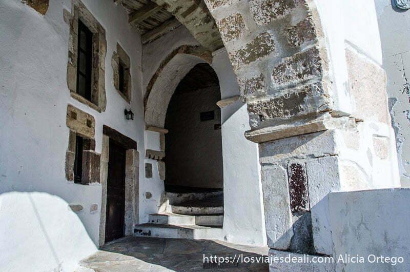 escaleras que suben hacia un arco de piedra en la capital de naxos