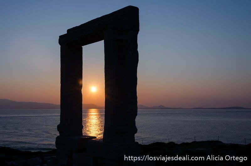 portara del templo de apolo con sol en el centro a punto de ponerse en el mar capital de naxos