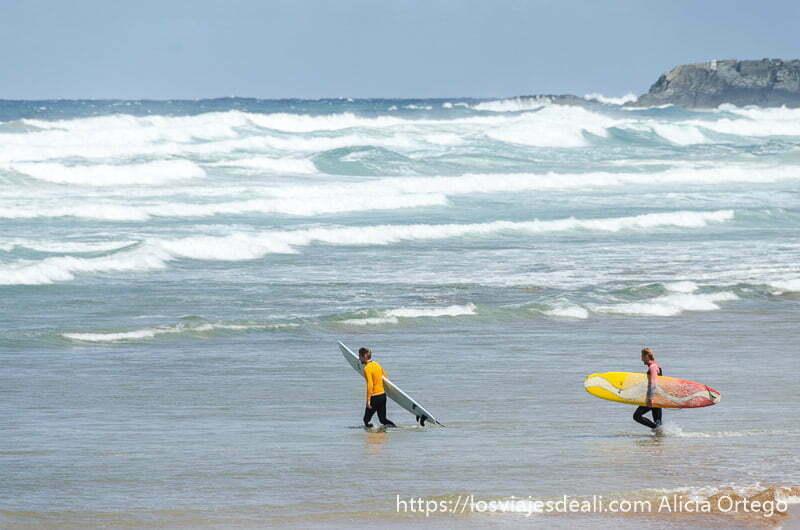 dos surfistas entrando en el mar con sus tablas en la playa de zaraut qué ver en getaria y alrededores