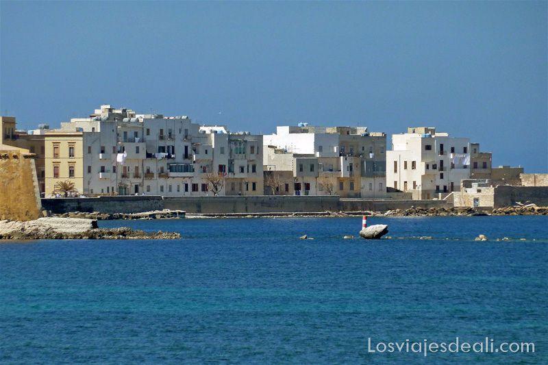 línea de casas blancas al borde del mar azul en Trápani en semana santa