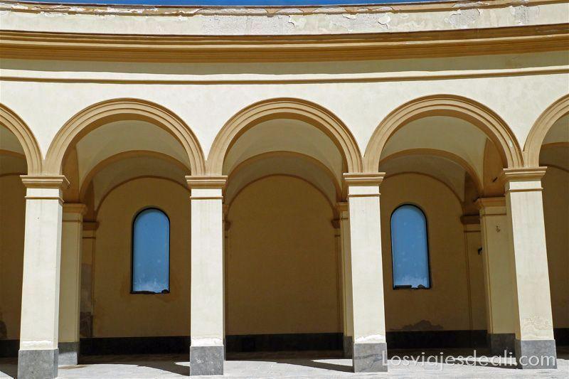 arcos de color beige con ventanas que dan al cielo azul Trápani en semana santa