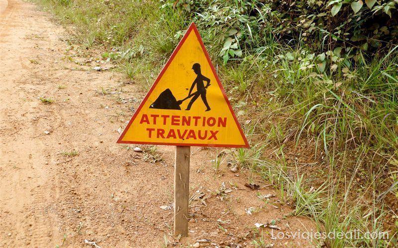 señal de peligro de obras en el margen de una pista forestal de la selva camerunesa