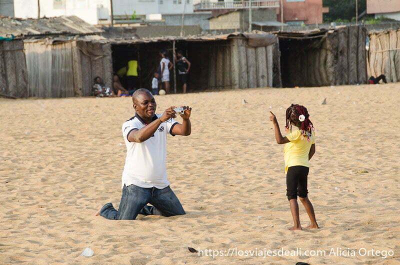 padre arrodillado en la arena hace foto a su hija que posa con sus trencitas en la playa de cotonou