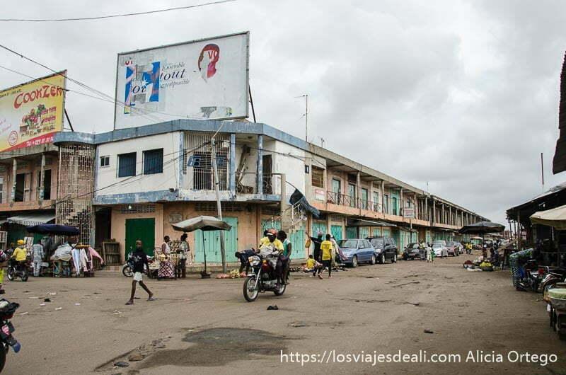 calle de mercado de cotonou medio vacía con moto pasando delante de edificio de tiendas que hace esquina