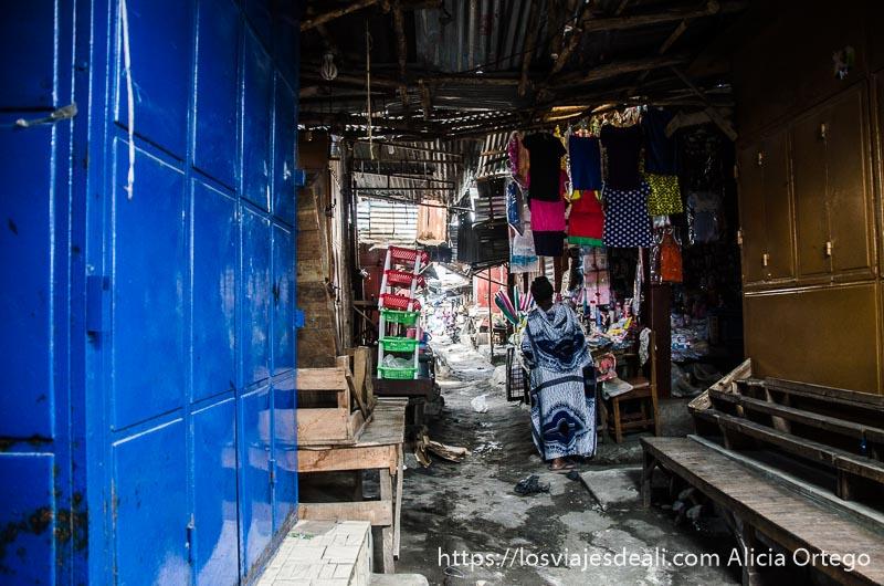 calle techada con tiendas medio cerradas y una mujer al fondo en mercado de cotonou