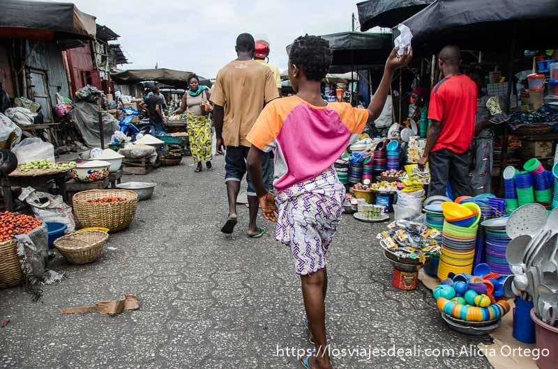 niña caminando por el centro de calle del mercado de cotonou