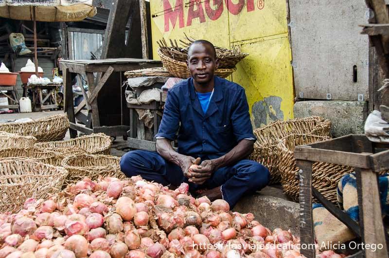 vendedor de cebollas posando para la foto en el mercado de cotonou