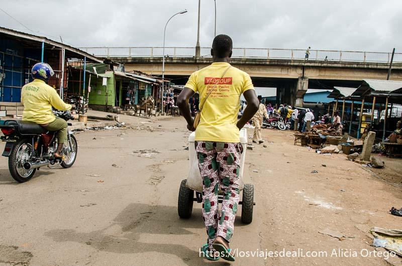 hombre con camiseta amarilla empujando carrito hacia el puente martin luther king de cotonou