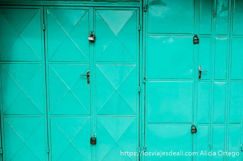 puerta metálica pintada de verde con candados en el mercado de cotonou