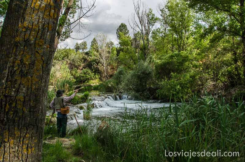 pescador tirando la caña al río bajo un gran árbol que le da sombra fin de semana de actividades