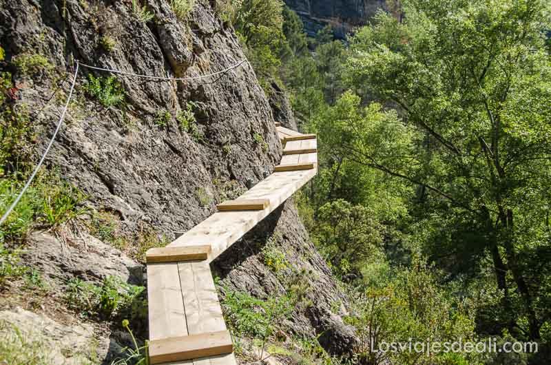 pasarela de madera con cable en la roca para sujetarse y sin barandilla en el lado del abismo en vía ferrata de cuenca