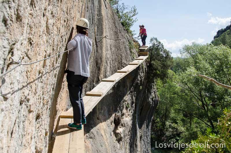 chica andando por  pasarela de madera sujetándose al cable que hay en la pared de roca vertical fin de semana de actividades