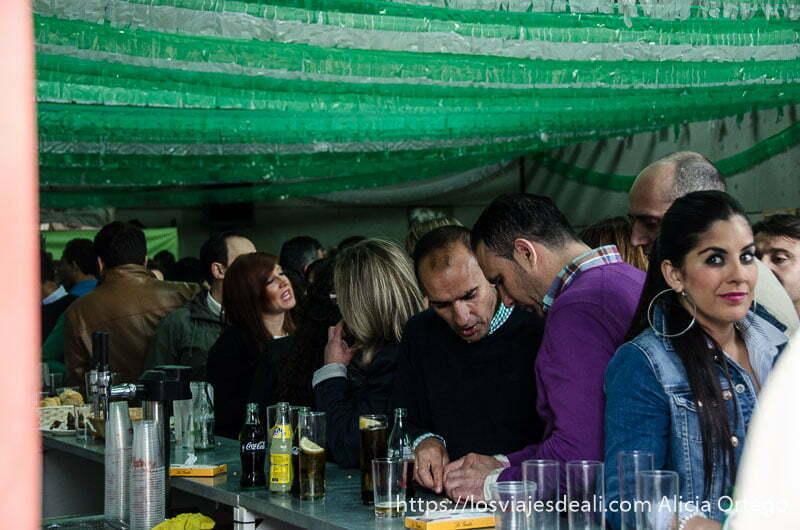 caseta de feria llena de gente junto a la barra de bar gastronomía extremeña