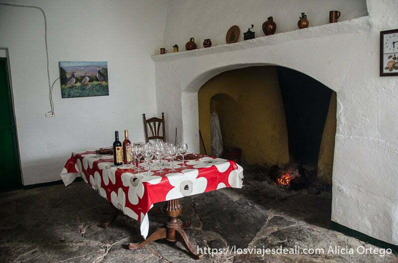 mesa llena de copas de vino junto a gran chimenea con paredes blancas en finca de la dehesa gastronomía extremeña