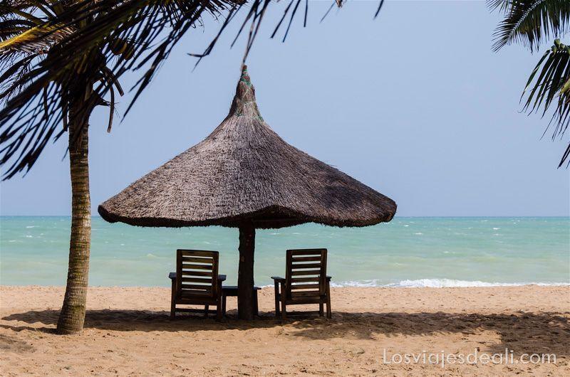 sombrilla de paja con dos hamacas y una palmera con cocos al lado. Al fondo el mar con color turquesa, en las playas de Benin
