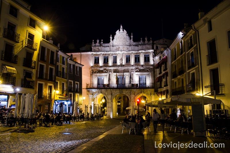plaza mayor iluminada por la noche con gente en las terrazas de los bares y la fachada del ayuntamiento al fondo iluminada qué ver en la provincia de cuenca