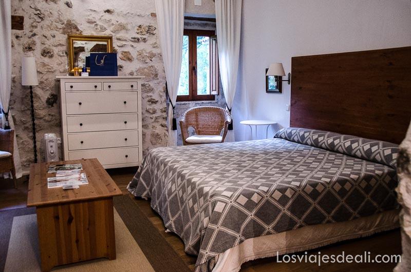 habitación del balneario de solán de cabras con gran cama y cómoda blanca qué ver en la provincia de cuenca