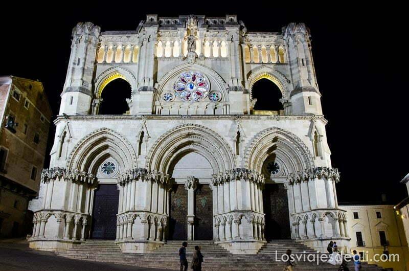fachada de la catedral de cuenca con tres grandes arcos por la noche iluminada