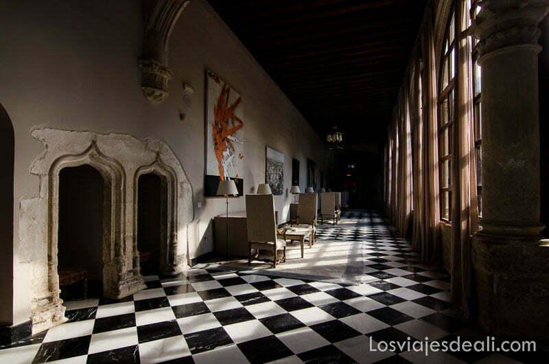 galería del parador de cuenca que da al patio interior con suelo ajedrezado y luz que entra por los ventanales góticos