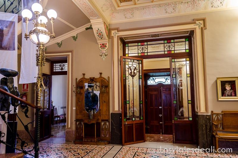 vestíbulo de can prunera con lámparas y vidrieras modernistas