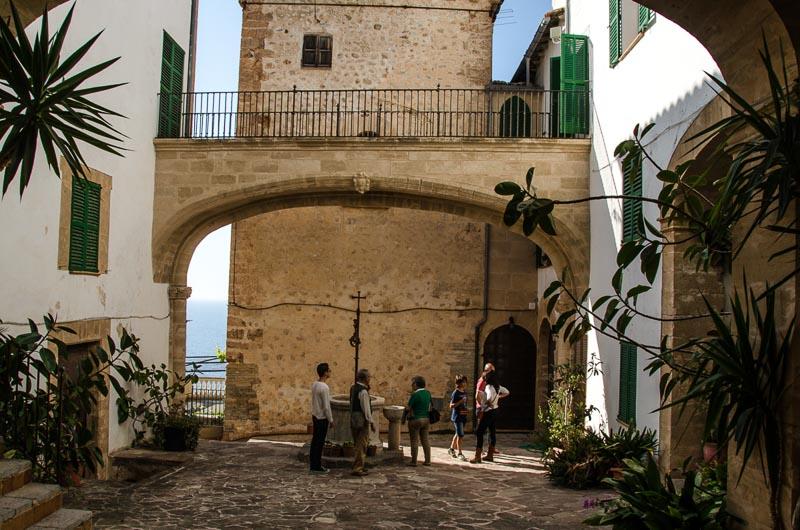 plaza interior con gran arco con pasarela arriba y pozo debajo en banyalbufar palma de mallorca