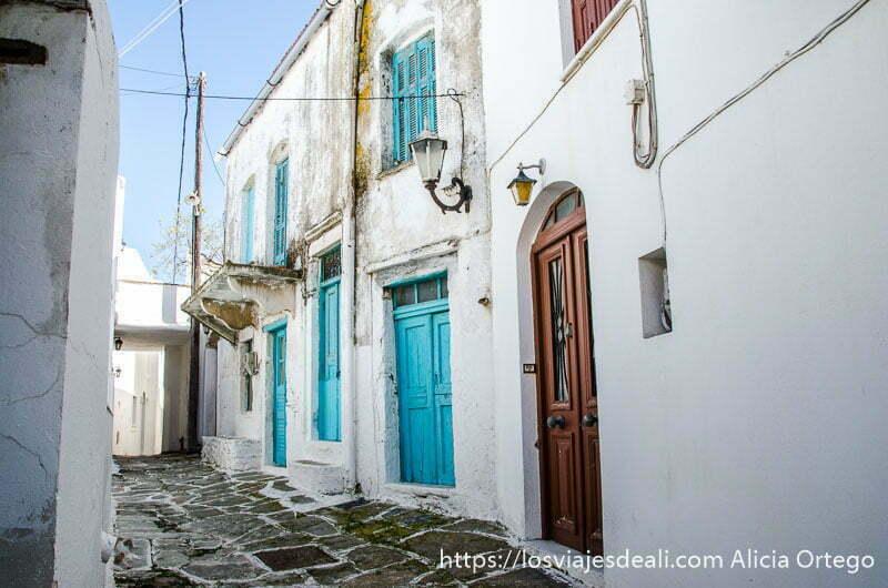 calle empedrada con casas blancas y puertas y ventanas azules en un pueblo de naxos