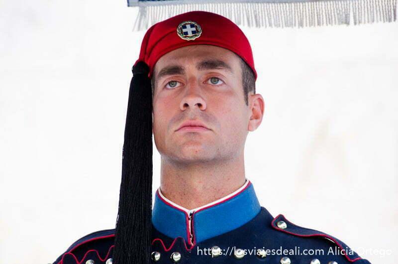 retrato de soldado griego mirando al frente con gorro rojo y uniforme de cuello azul en plaza de sintagma
