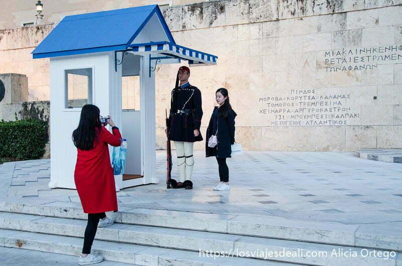 dos turistas japonesas haciendo foto con soldado griego en plaza sintagma lugares de interés en Atenas