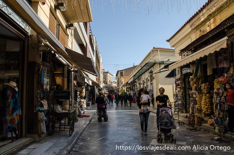 calle de plaka con tiendas y una pareja paseando con carrito de bebé lugares de interés en atenas